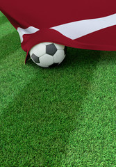 Soccer ball and national flag of Latvia,  green grass