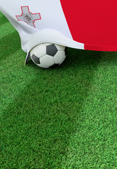 Soccer ball and national flag of Malta,  green grass