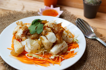 Fried squid serve with vegetable and sauce.
