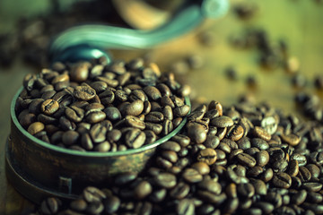 Coffee. Coffee beans. Roasted coffee beans spilled freely on a wooden table. Coffee beans in a dish for ground coffee.