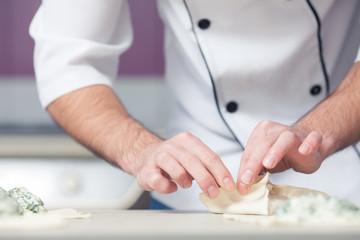 Vegetarian bakery concept. Chef cook in uniform putting filler