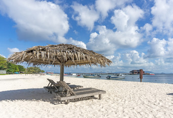 Dreamy beach with sun loungers under a beach umbrella at Mabul Island, Sabah Malaysia.