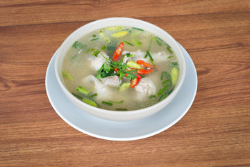 Chicken soup isolated on wood background.