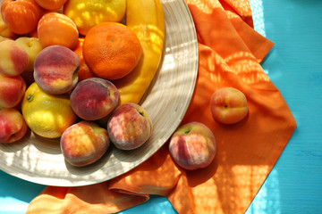 Heap of fresh fruits on tray on wooden table close up