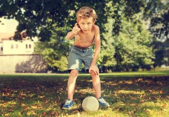 Boy in park ready to kick ball