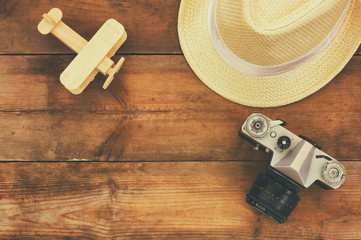 top view image of wood aeroplane, fedora hat and old camera over wooden table