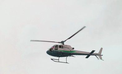 civil helicopter flies in the sky and carries tourists