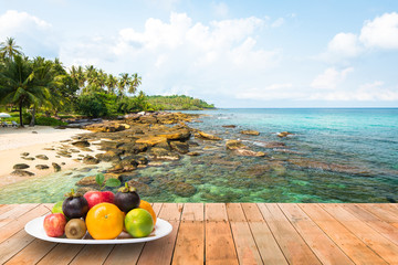 Wall Mural - Plate of fresh fruit put on a wooden planks at the beautiful beach