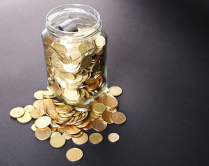 Glass jar with coins on dark background