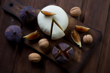 Top view of fresh adygea cheese, ripe fig fruits and walnuts