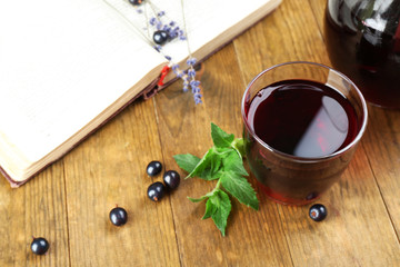 Fresh currant juice with berries and book on table close up