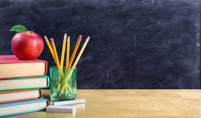 Apple On Stack Of Books With Pencils And Blank Chalkboard