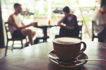 Cup of coffee on table in cafe, vintage or retro color effect - shallow depth of field