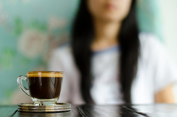 The cup of coffee on the table with woman background