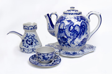 Porcelain teapot, cup, saucer and creamer in folk style painted blue on white background