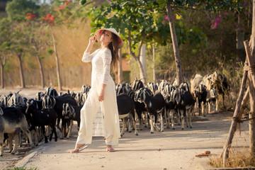 blonde girl in Vietnamese dress stands against flock