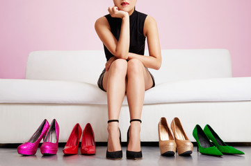 Woman thinking on the sofa with many shoes.Beautiful colorful high heels.