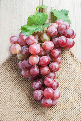 Red grape with natural sackcloth on wooden table