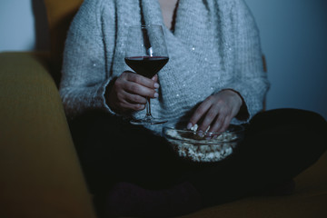 Close up of overweight woman watching TV with glass of wine and