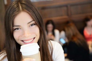Portrait of young woman having coffee. Smiling beautiful mixed race Asian / Caucasian female is with disposable cup. She is in coffee shop.