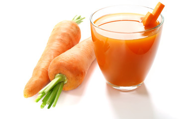 Glass of carrot juice with vegetable slices with vegetables isolated on white