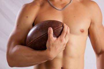 Shirtless man holding a football