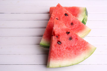 Slices of ripe watermelon on wooden background