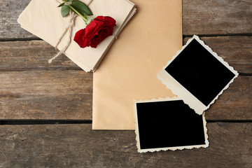 Blank old photos with letters and beautiful rose on wooden background