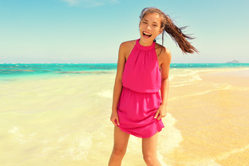 Wall Mural - Portrait of happy young woman in pink dress standing at beach. Beautiful mixed race Asian / Caucasian female is enjoying her summer vacation. Carefree woman is laughing while standing on shore.