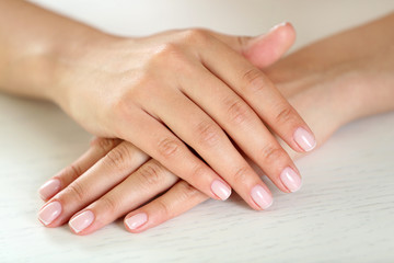 Woman hands with french manicure on table close-up