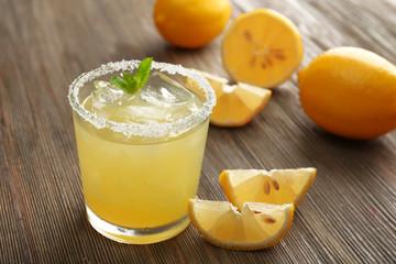 Glass of lemon juice on wooden table, closeup
