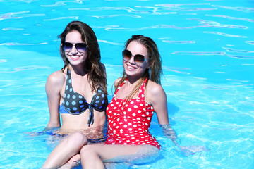 Two young girls enjoying in swimming pool at summertime