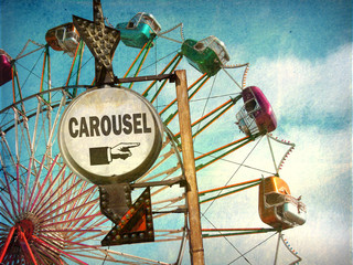 aged and worn vintage photo of carousel with ferris wheel
