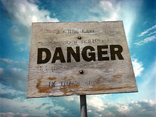 aged and worn vintage photo of wooden danger sign