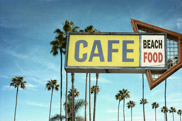 aged and worn vintage photo of cafe sign on beach with palm trees