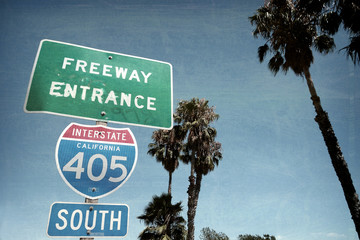 aged and worn vintage photo of freeway sign with palm trees