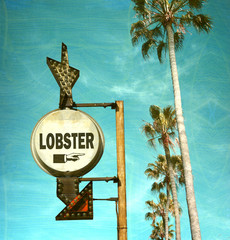 aged and worn vintage photo of lobster sign and palm trees