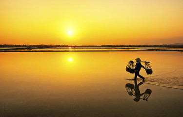 Farmer going home after a hard working day in Hon Khoi salt field, Nha Trang, Vietnam