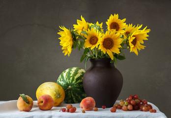Букет подсолнухов в глиняном кувшине и фрукты на столе.