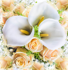 Wall Mural - Bouquet for the bride of yellow roses and white calla lilies, floral background.