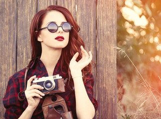 girl in plaid dress with camera and sunglasses