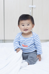 Cute Chinese baby boy sitting on a white blanket