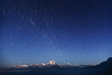 Night laconic landscape. Starry sky over the snowy mountains.