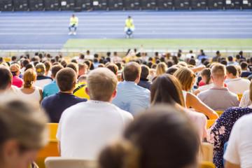 Spectators sit in the stadium