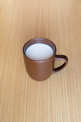 A mug cup containing a hot white milk on wooden table