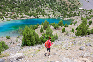 Hiker Walking Down to Lake Person Sporty Clothing and Gear Descending to Amazing colored Mountain Lake
