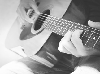 Details of performer man hands playing acoustic guitar musical, black and white photo- B&W