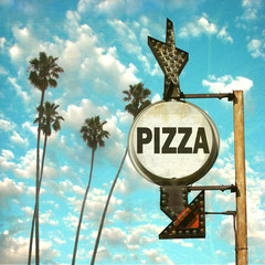 aged and worn vintage photo of pizza sign with palm trees