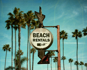 aged and worn vintage photo of beach rentals sign with palm trees