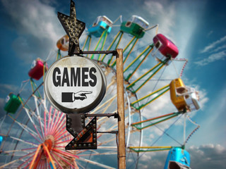 aged and worn vintage photo of games sign at carnival with ferris wheel